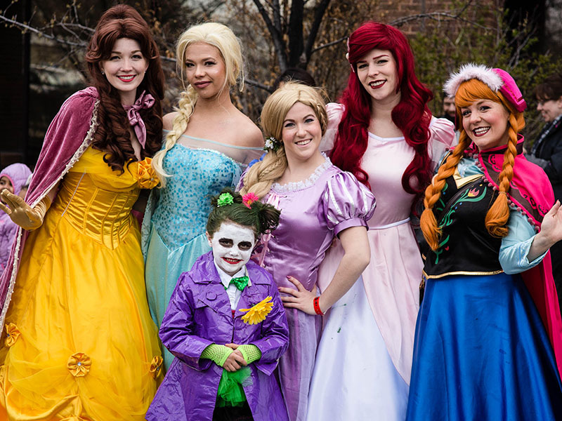 Cosplayers dressed as Disney princesses, and one little Joker, take part in the POW! Parade of Wonders