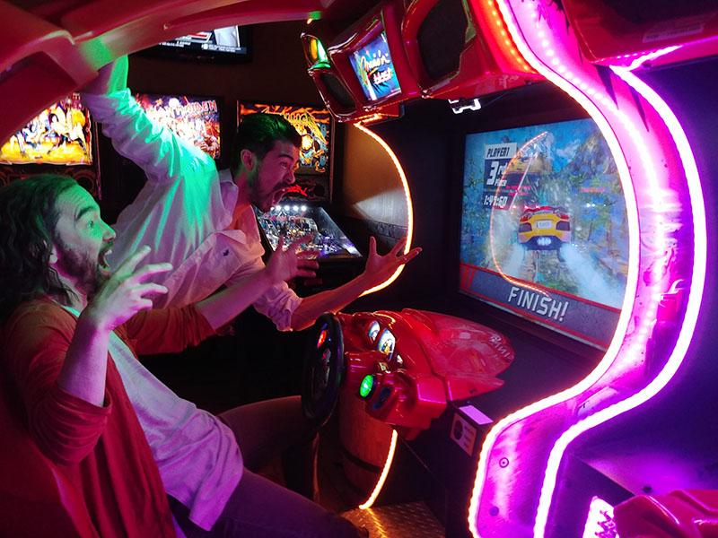 Mark Kunji Ikeda and Richard Lee play a racing game in an arcade