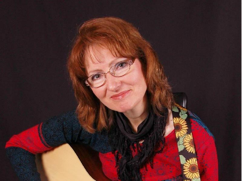 A photo of Doreen Vanderstoop holding a guitar