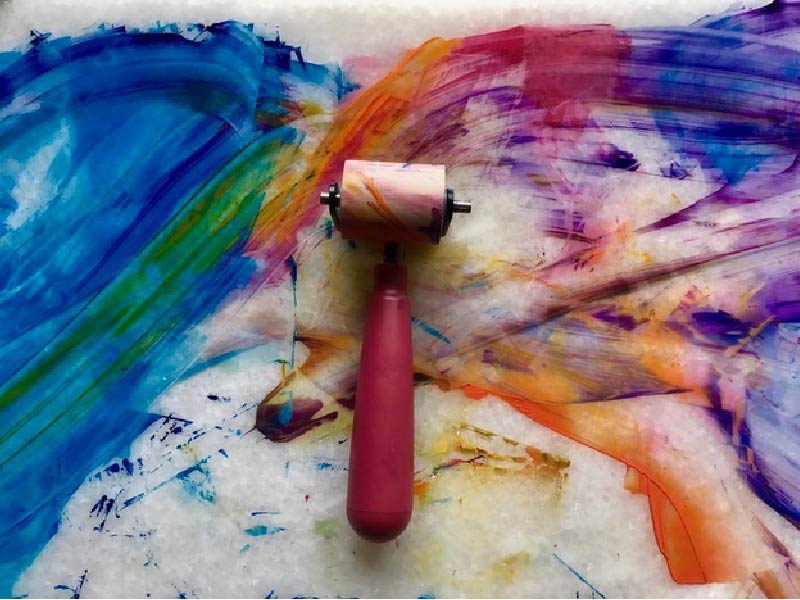 Photo of paint roller on top of abstract painting