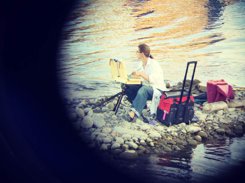 A photo of Leslie Sweder painting by the river