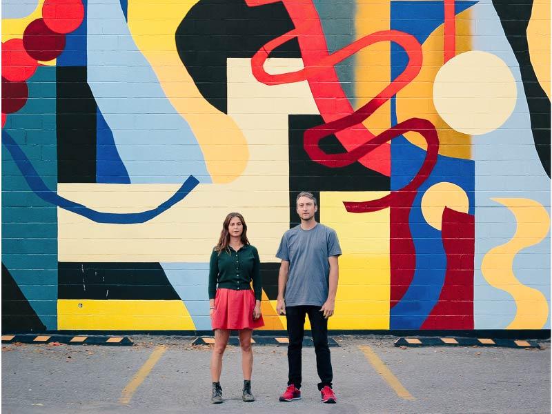NASARIMBA artists Mikhail Miller and Rachel Ziriada stand in front of their mural