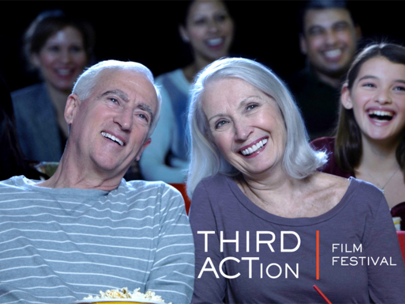 A photo of two older people enjoying a film screening