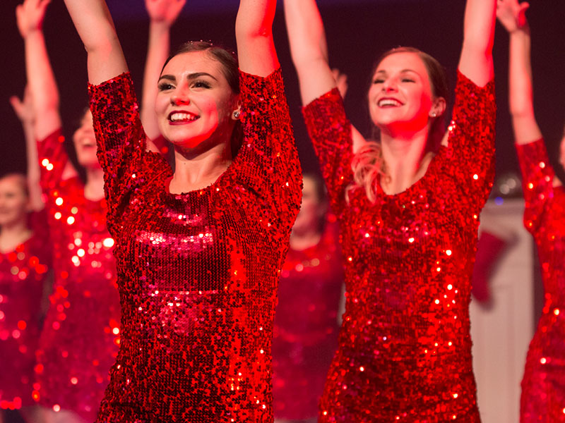 The SHOW performers in red dresses