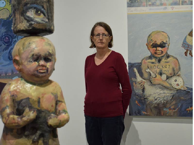 A photo of Violet Costello with artwork