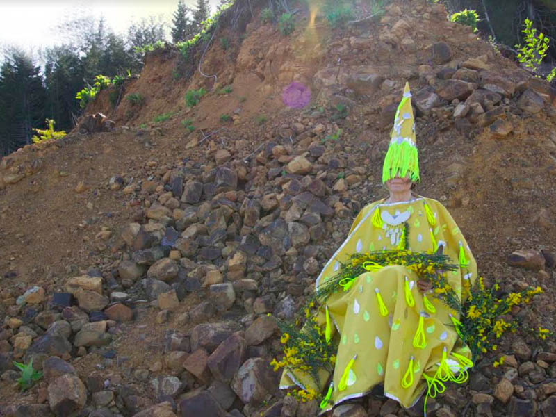A person wears a yellow costume on a rocky hill