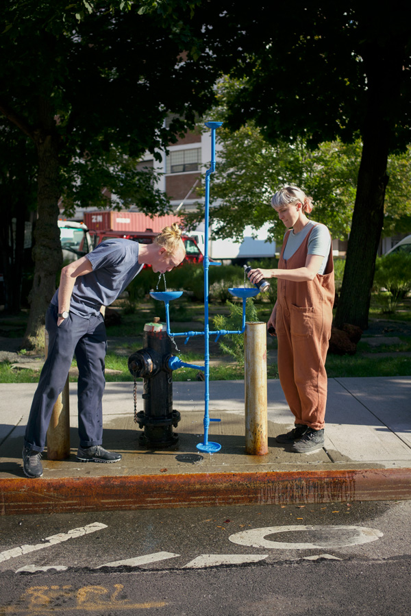 A photo of Tei Carpenter and Christopher Woebken drinking out of Hydrants for All, New Public Hydrant