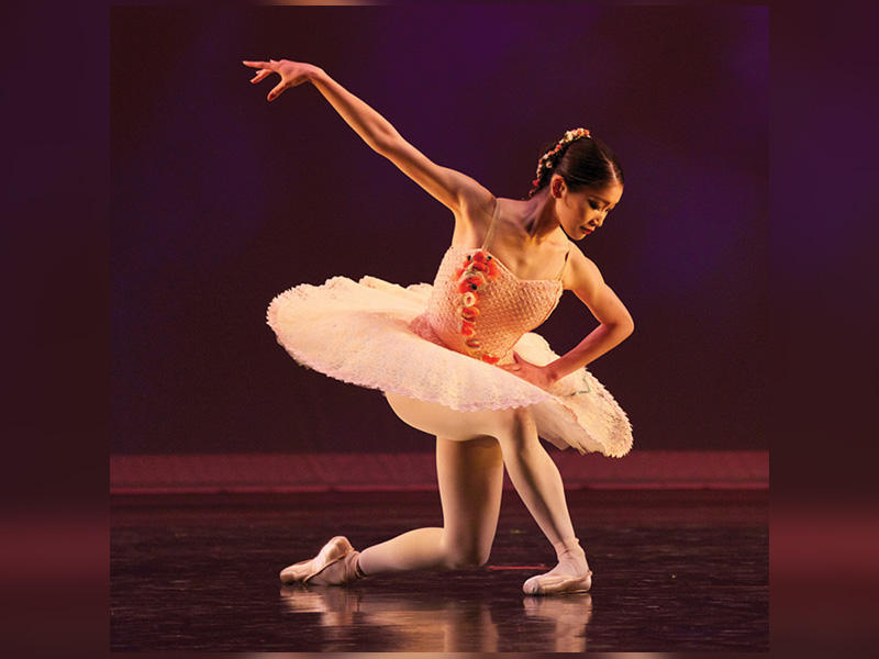 A young dancer performs in a pink tutu