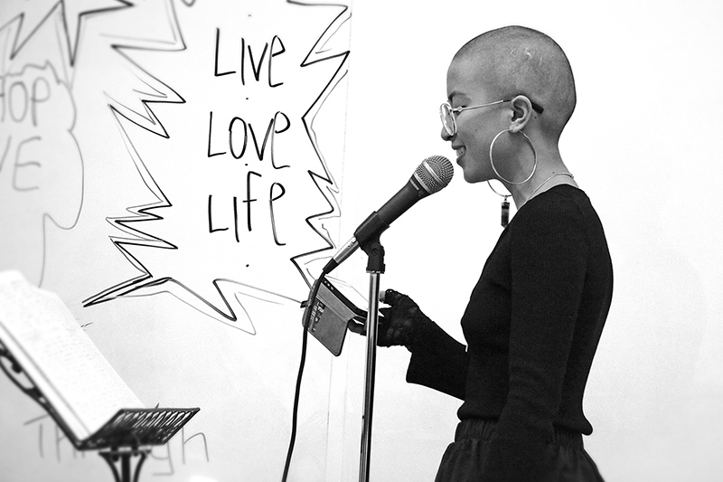 "v.ila the Poet in front of a graphic that says, ""Live Love Life"""