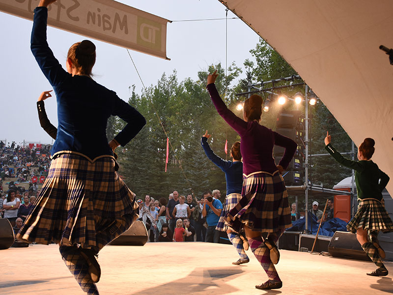 A photo from behind four Highland dancers and the audience watching them perform