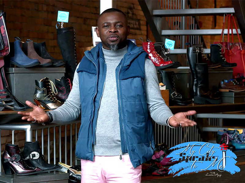 Lanre Ajayi stands among the shoes at John Fluevog's Calgary store