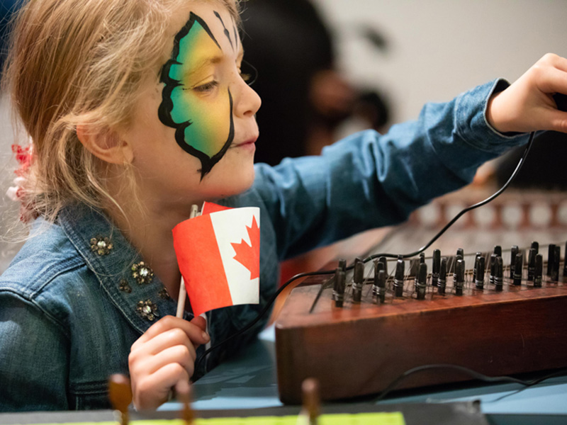 A child with a painted face holds a Canadian flag while exploring Studio Bell