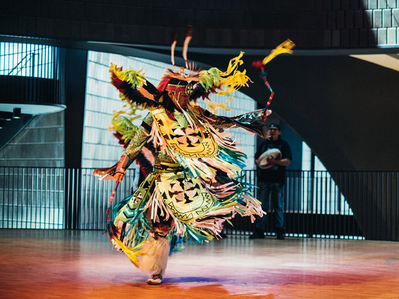 An Indigenous dancer performs in full regalia