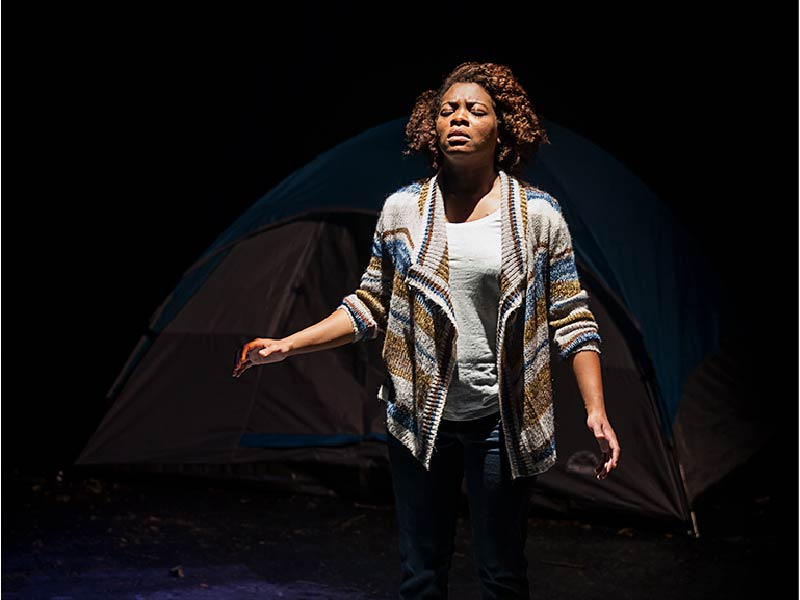 Woman stands in front of tent on production by Sage Theatre