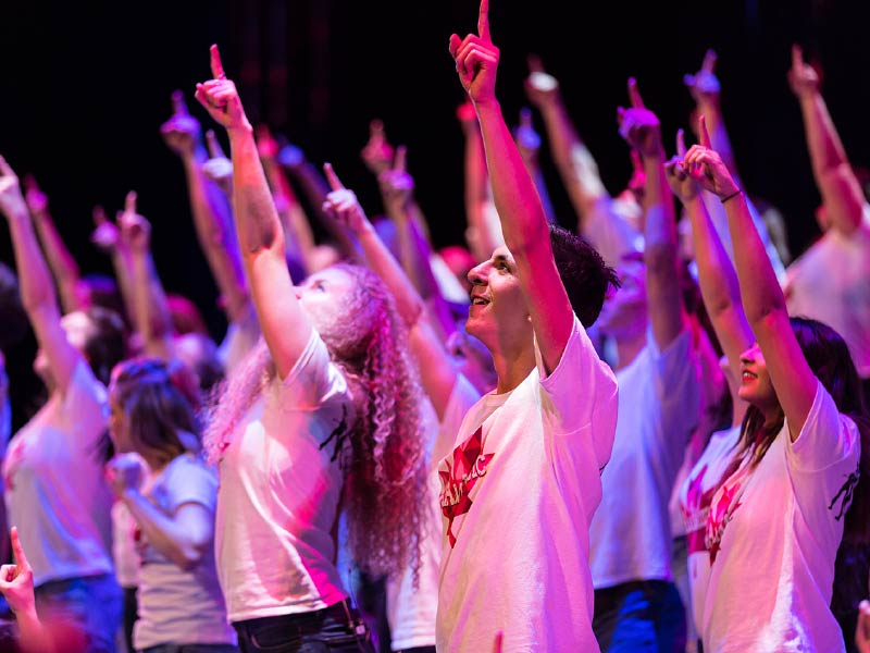 Youth Singers of Calgary performers raise their hands