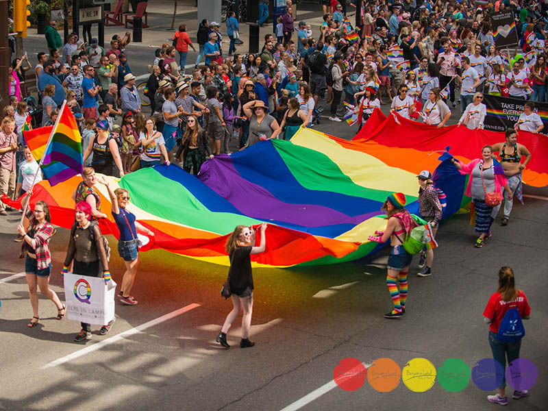 Participants at the Calgary Pride Parade hold a giant rainbow flag