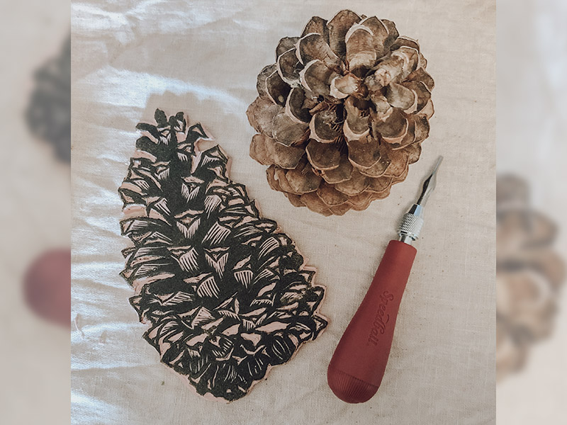 A lino block carving, tool, and pinecone