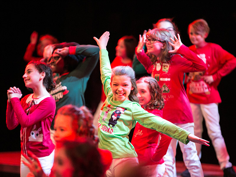 Youth Singers of Calgary members on stage in Christmas pajamas