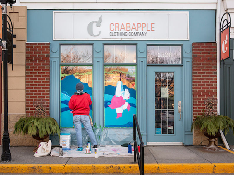 Mike Hooves works on the window at Crabapple Clothing Company