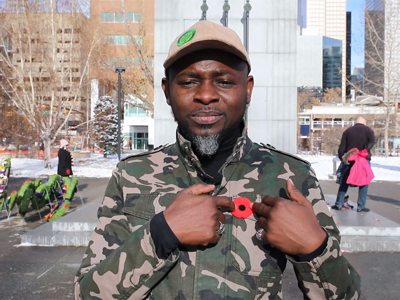 Lanre Ajayi points at his poppy at the Remembrance Day at Memorial Park