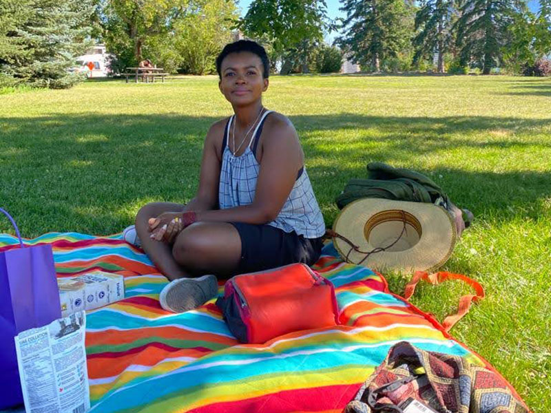 Stephanie Solomon sitting on a picnic blanket on a sunny summer day