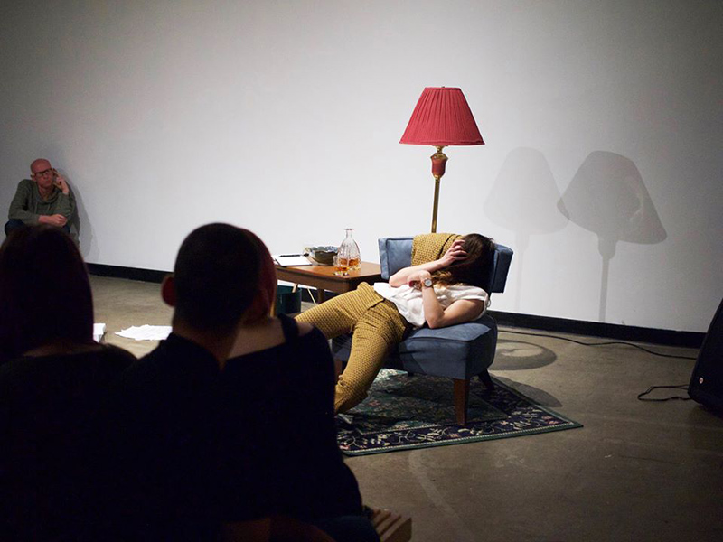 A person slouches in a chair in a performance piece