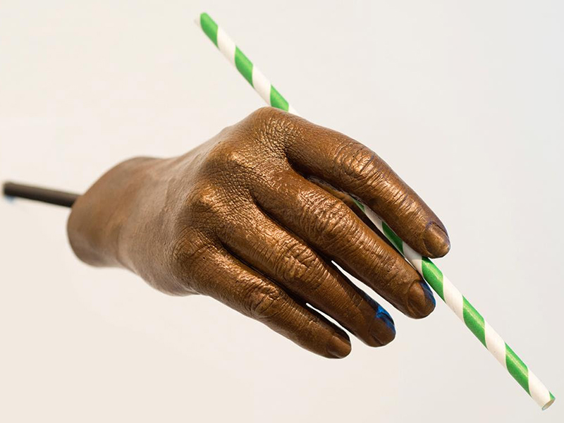 A sculpture of a hand holding a paper straw