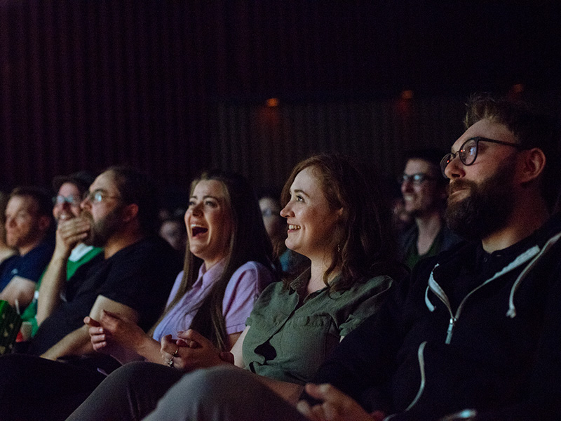 Audience members laughing in a theatre