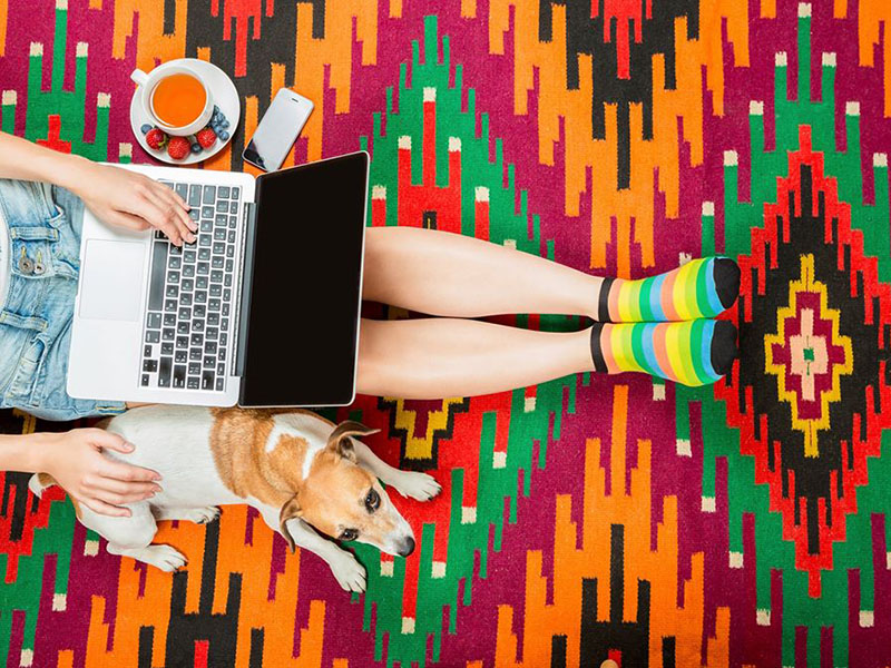 A photo of a person sitting on a colourful rug with their laptop on their lap