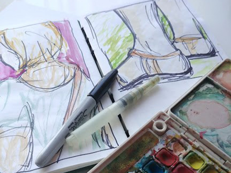 A photo of water colour paints and sketches