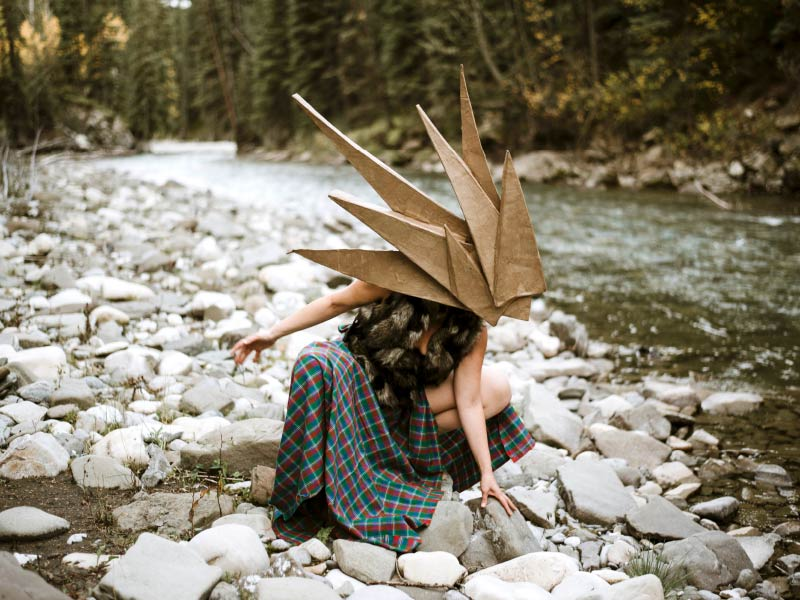 Person wearing pointy headpiece kneeling by river