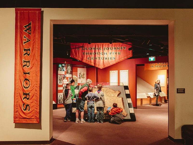 A Scout troop explores Warriors: A Global Journey Through Five Centuries at Glenbow