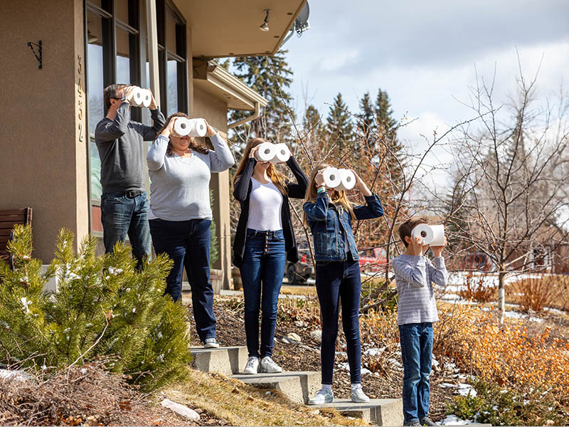 A family looks through toilet paper rolls on their front steps in Porchtraits by Neil Zeller