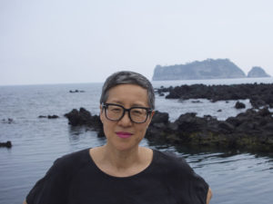 A photo of Jin-me Yoon next to water