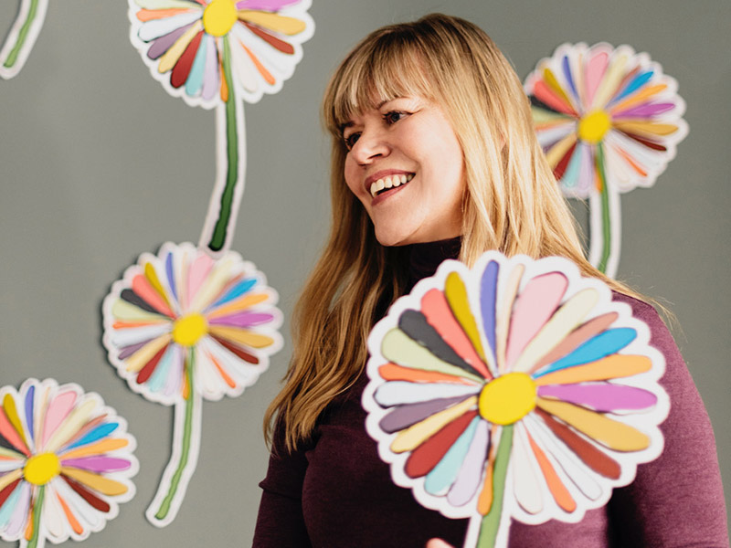 A photo of Shelley Youngblut with paper daisies
