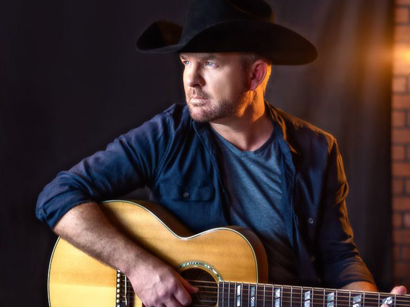 A promo photo of Bobby Wills in a cowboy hat with a guitar