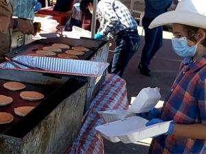 Volunteers wear PPE and run a drive-through pancake breakfast