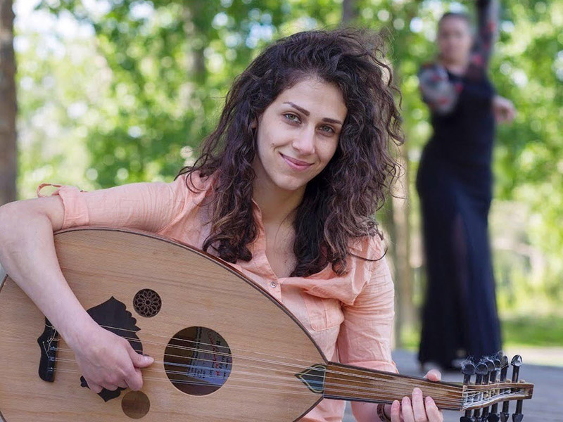 A photo of Aya Mhana holding an oud with a dancer in the background
