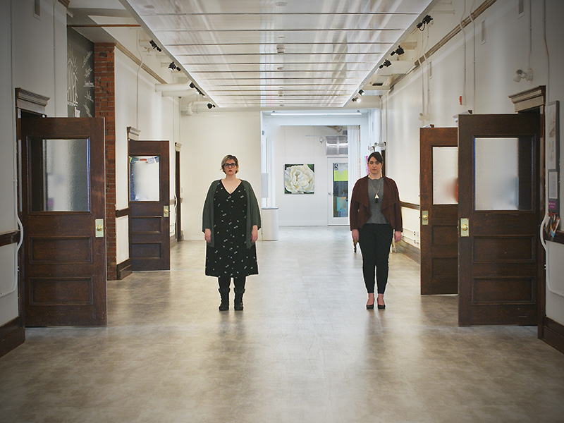 Two women in a school hallway with the doors around them all open