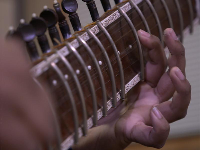 A still of Ayush Gosh playing a sitar