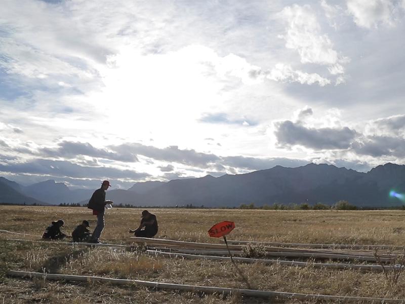 Stoney Nakoda AV Club members in a field near the mountains