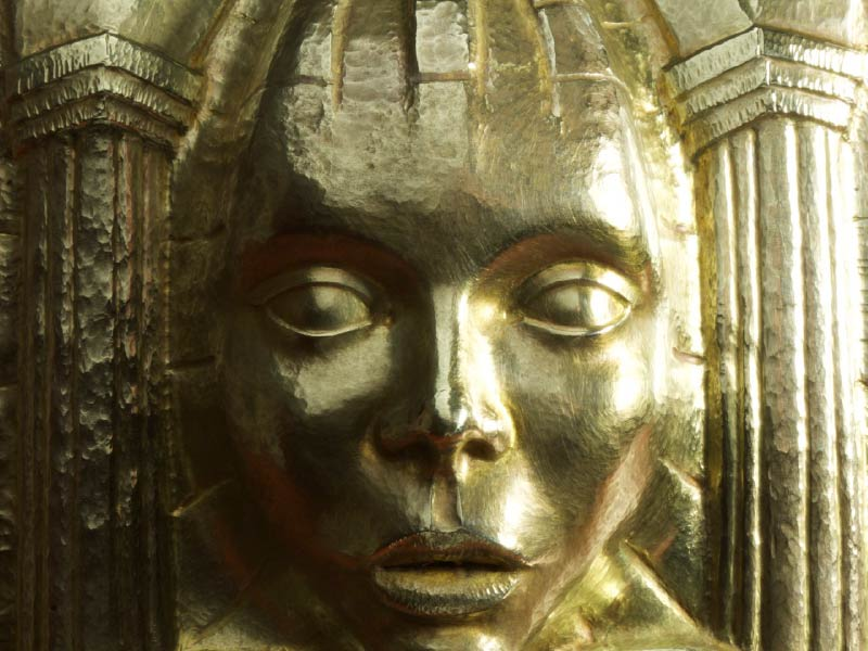 Brass sculpture of face and columns