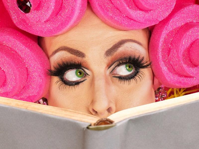 A drag queen reading a book