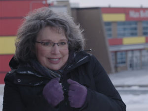 Julie Freedman Smith in front of a snowy Max Bell Arena