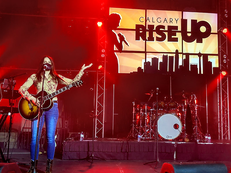 Emily Triggs on stage in front of a RISE UP Calgary logo