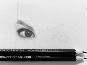 A pencil drawing of Grace Kelly in process with two pencils on the paper
