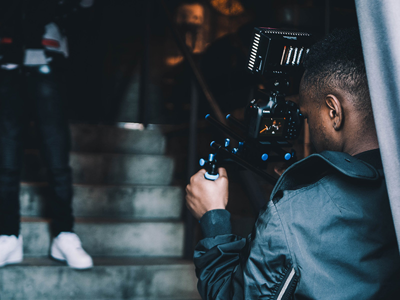 A behind the scenes photo of a Black person behind a film camera