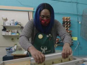 Adora Nwofor pulls ink across a silk screen to make a print