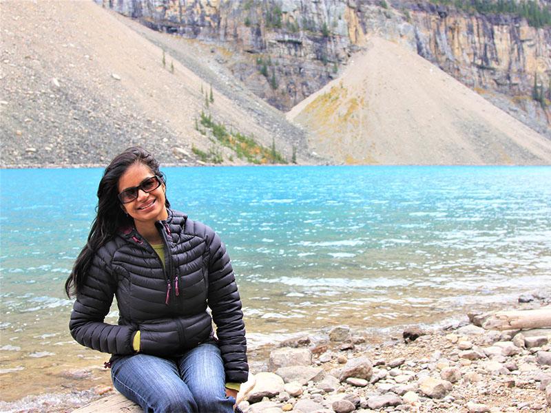 Gayathri Shuklasitting next to a mountain lake