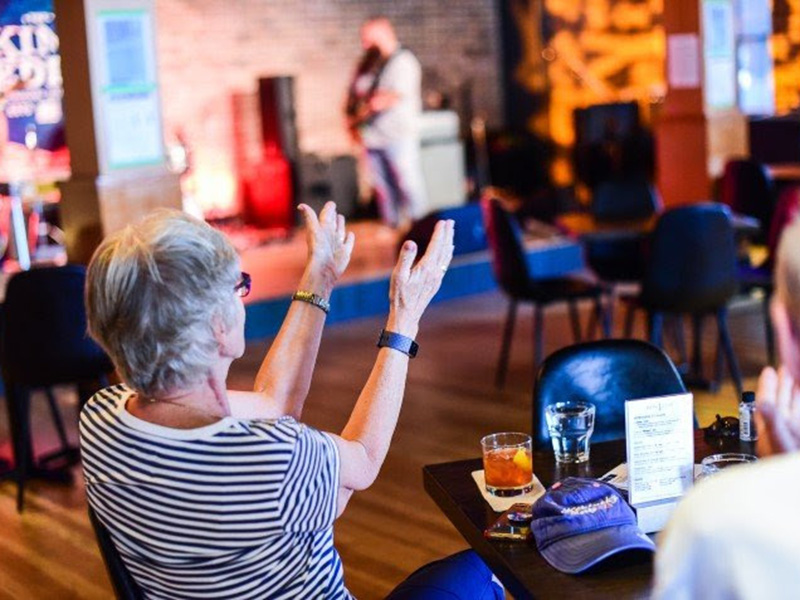 An older person clapping at a live performance at the King Eddy